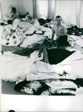 Year ? Portrait of  an Italian designer popular in the 1940s and 1950s Emilio Schuberth sitting on floor and looking at the dresses spread on the floor.