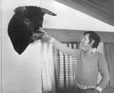 El Cordobés  touching buffalo's head placed on the wall.