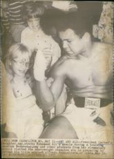 President Carter's daughter Amy checks Muhammad Ali's muscle