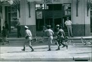 Soldiers running in street due to emergency,1961.