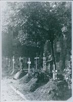 "Man and woman standing in a graveyard in Poland.  ""Poland __ ""  1945"