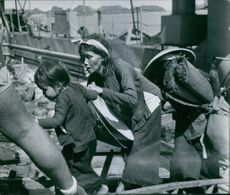 A photo of a woman helping her child in a hurry walk while a woman is behind her carrying a load.