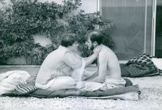 Vintage photo of a man and a woman sitting in the outdoor, the woman gently holding the neck of the man.