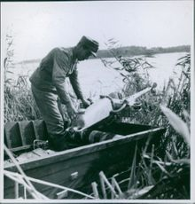 Finnish soldier in the boat touching on the motor in Sortavala during the war in Finland, 1941.