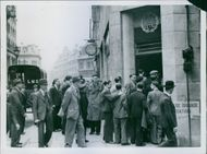 People gathered in street in front of the building and communicating with each other.