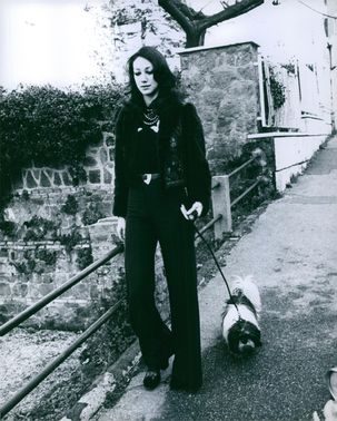 American actress and model Marisa Berenson walking with her black and white dog, January 2, 1973.