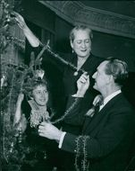 Einar Beyron and wife Olga Hertzberg decorating the Christmas tree with their daughter. 1955.