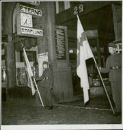 Two soldiers standing outside the building holding firm the flags. 1939