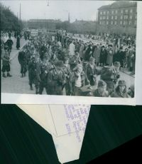 People gathered and walking together in the street of Denmark during WWII.