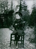 Pierre Marcilhacy as a young boy sitting on a chair outdoor.