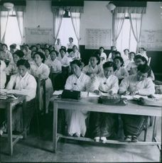 Women are quietly attending class.
