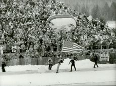 Parachutist landing with the American flag during the 1980 Winter Olympics