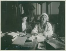Two woman sitting in front of table and facing camera, 27 September 1920.