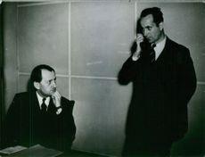 French novelist André Malraux is thinking something, while a men have standing