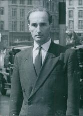 Richard Nunn standing in street and looking at the camera.