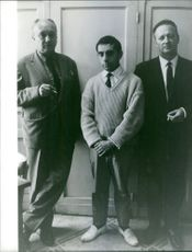 Men standing and smoking cigarette.