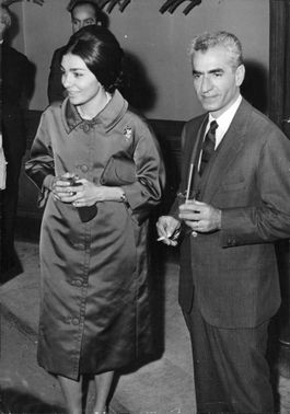 Farah Pahlavi and Mohammad Reza Shah Pahlavi having conversation with somebody in an event.