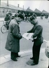 Man buying newspaper from a seller in England in 1954.