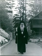 1967 A holy man walking alone on the road.