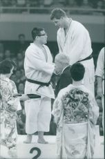 Martial arts winners congratulating each other by shaking hands as they receive their awards.  Taken - Oct. 1964