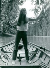 A woman standing on the boat, touching the leaves of a tree.