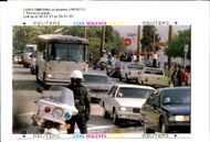 A Los Angeles Police Motorcycle officer stops traffic as a 14-Vehicle motorcade.