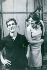 A man standing with a woman, smiling.