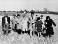 Prince Akihito and Princess Michiko of Japan walking on a grassy land together with other people.