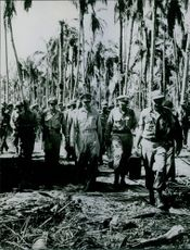 Douglas MacArthur walking in forest with other soldiers. 1964