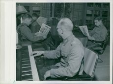 Soldiers sitting and reading newspapers while other playing a piano during First World War, 1940.
