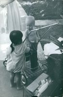 A child is standing on a cart beside another child.