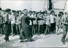 Young boys gathered in street, a man trying to control them.