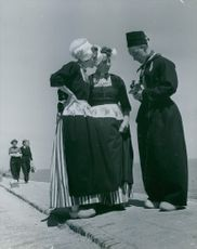 Man showing his camera to two women.
