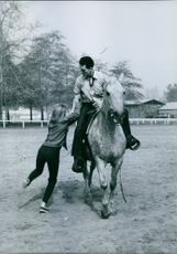 Buzz picking up Marta Kristen to get on the horse.