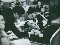People in assembly, two men shaking hand. 1960