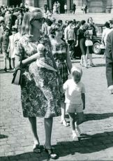 Queen Paola of Belgium walking with her son.