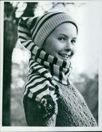 Young girl posing and wearing warm clothing.