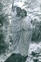Horst Buchholz wrapped in a piece of clothing with unknown woman.