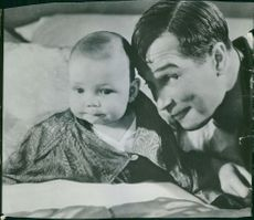 Maurice Chevalier playing with a small child.
