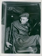 PTE A.J. Crilly of London packing his sten gun, when about to start his night driving duty.
