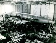An aircraft being manufactured in an industry.