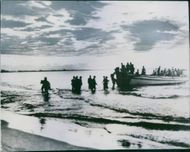 Soldiers getting into the boat in sea.