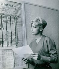 Michele Dimitri holding a piece of paper while looking at a chart posted on the board, 1959.