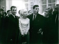 Jerry Lewis standing together with Tony Curtis and other people.