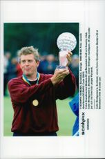 Golf player Colin Montgomerie holds up the trophy after winning the Volvo Scandinavian Masters 1999