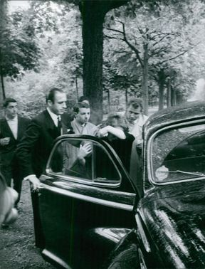 Bettina Graziani getting into car, trying to escape from rain. Photo taken on March 17,1960.