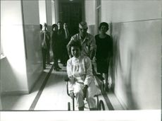 Woman sitting on wheel chair brought in the hospital _ Barbara Power is one of the survivors of the Plane crash in Rome in 1964