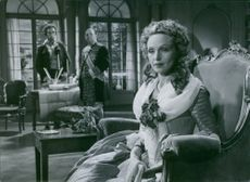 """A scene in the film """"Kungajakt"""" 1944 Swedish drama film .  Inga Tidblad sits on a chair while the two men (Holger Löwenadler and Erik 'Bullen' Berglund stood  in a far side of the room looking at her."""
