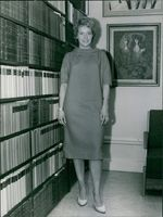 Woman standing beside book shelves, looking towards the camera and smiling.