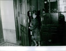Woman coming out from door.